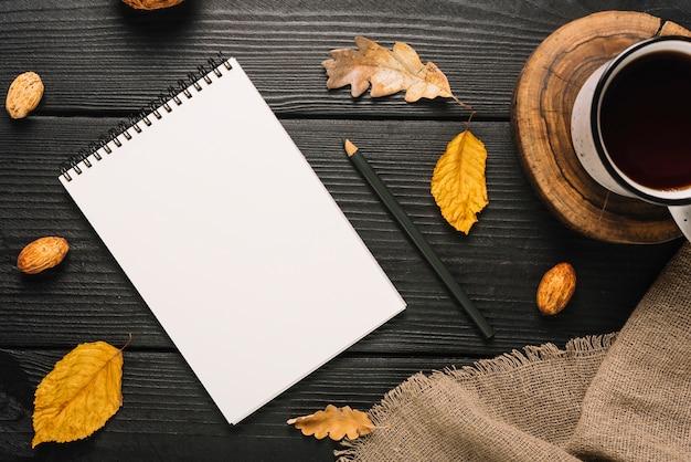 Artigos de papelaria e folhas perto de chá e pano Foto gratuita