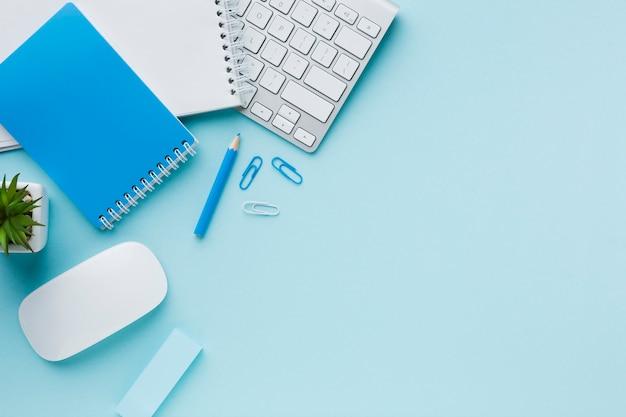 Artigos de papelaria e teclado azuis do escritório Foto gratuita