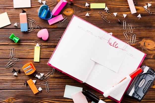 Artigos de papelaria em torno do caderno aberto com nota Foto gratuita
