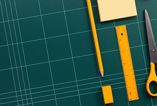 Artigos de papelaria laranja e tapete verde de corte close-up de imagens Foto Premium