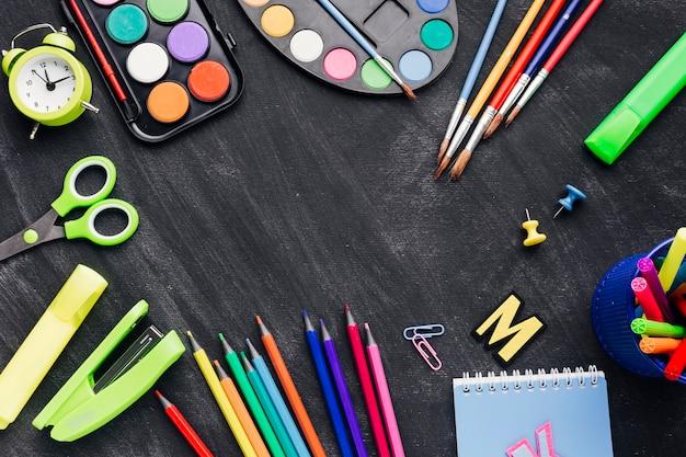Artigos de papelaria multicoloridos para criação em fundo cinza Foto gratuita
