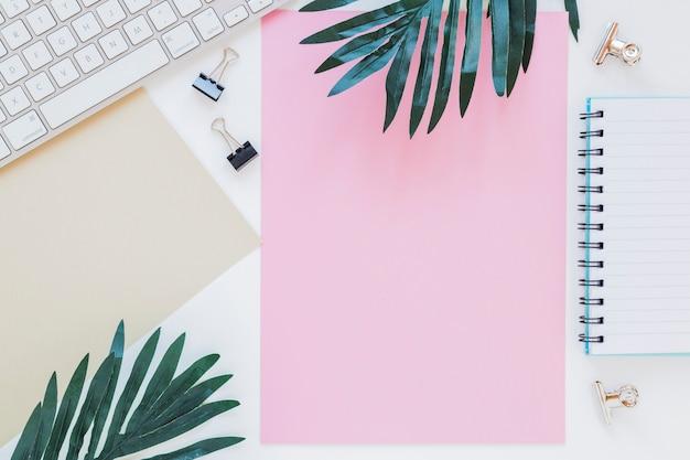 Artigos de papelaria perto de teclado e palmeiras Foto gratuita