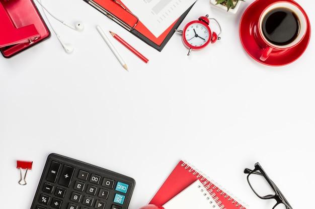 Artigos de papelaria vermelhos, despertador e calculadora na mesa branca Foto gratuita