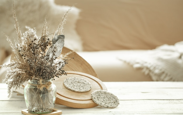 Artigos decorativos no interior aconchegante da sala, um vaso com flores secas na mesa de madeira clara. Foto gratuita