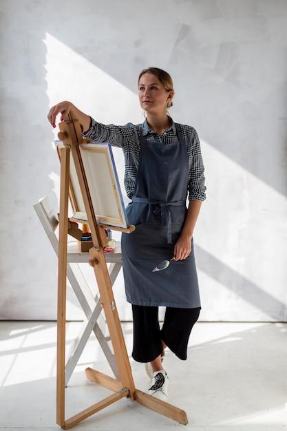 Artista de avental posando com cavalete e lona Foto gratuita