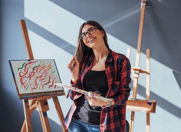 Artista de cabelos escuros, segurando um pincel na mão e desenha uma imagem sobre tela. Foto Premium