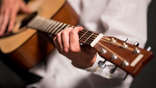 Artista de camisa branca tocando violão em close-up Foto gratuita
