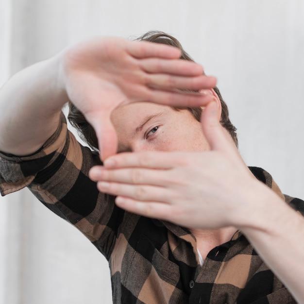 Artista de homem fazendo um quadro com os dedos close-up Foto gratuita