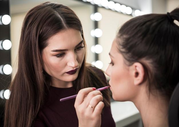 Artista de maquiagem aplicando batom Foto gratuita