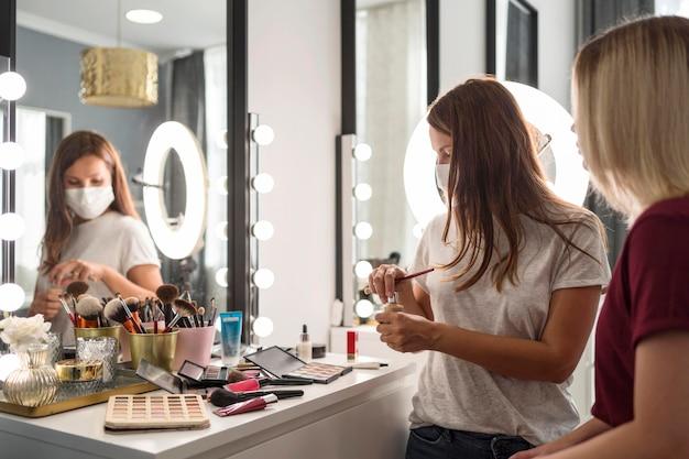 Artista de maquiagem usando máscara médica Foto gratuita