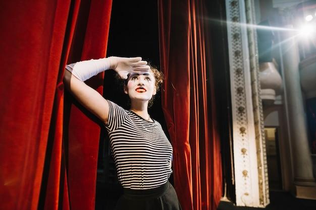 Artista de mímica feminina em pé perto da cortina vermelha, protegendo os olhos Foto gratuita