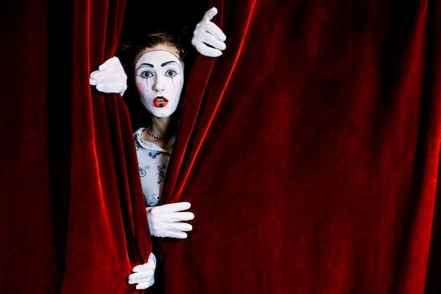 Artista de mímica feminina grave a espreitar da cortina vermelha Foto gratuita