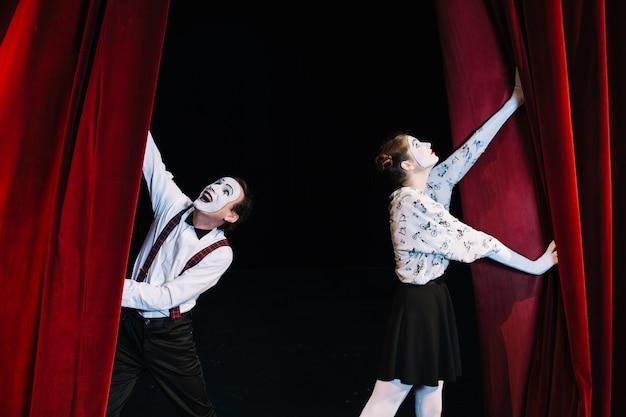 Artista de mímica masculina e feminina, empurrando a cortina vermelha de abertura Foto gratuita