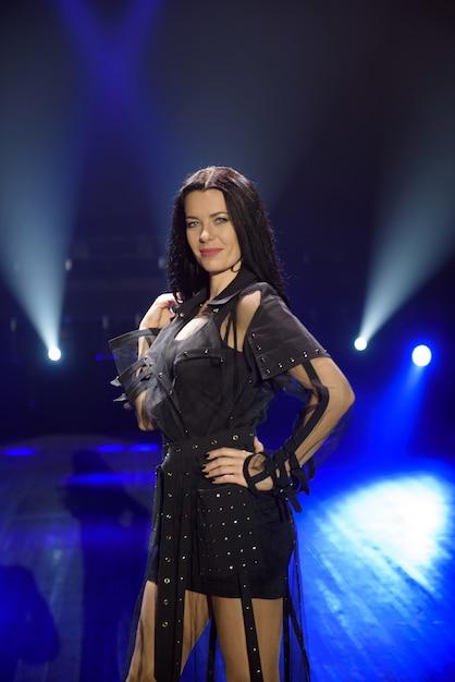 Artista feminina no palco em fundo escuro, fumaça, holofotes azuis Foto Premium