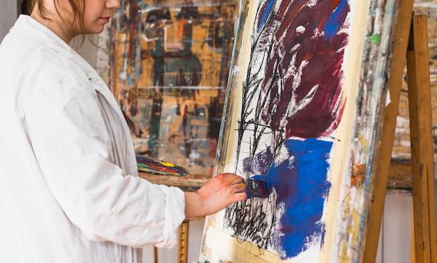 Artista feminina, pintura com pincel sobre tela na oficina Foto gratuita