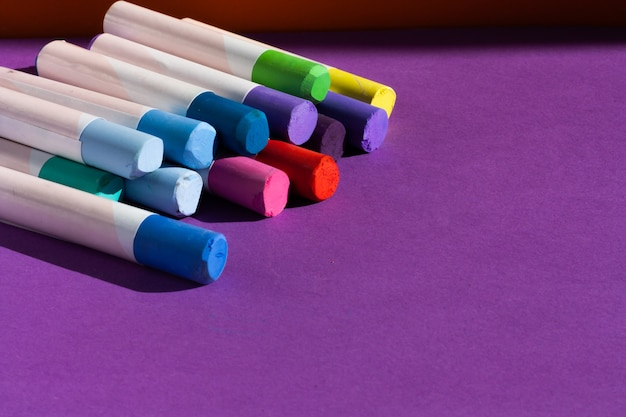 Artista giz sobre fundo lillac. ferramentas para lazer criativo e passatempo de pintura. copie o espaço. Foto Premium