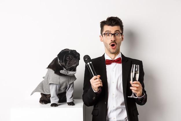 Artista masculino levantando a taça de champanhe, dando o microfone ao lindo cachorro preto, em pé sobre o branco. Foto Premium