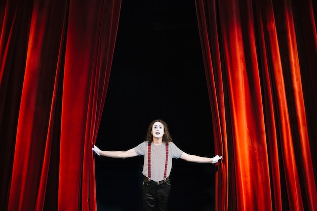 Artista masculino mímica no palco perto da cortina vermelha Foto gratuita