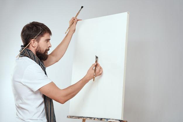 Artista masculino pinta uma imagem sobre tela com um cavalete Foto Premium