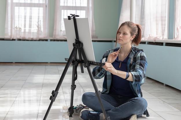 Artista menina pinta com tintas a óleo, sentado no chão de mármore. cavalete e lona branca ficam no chão de azulejos de mármore na sala com paredes verde-turquesa e verde claro. Foto Premium