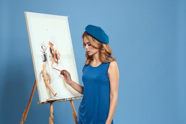 Artista mulher pinta sobre tela com um cavalete Foto Premium