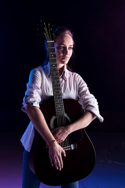 Artista no palco abraçando o violão Foto gratuita