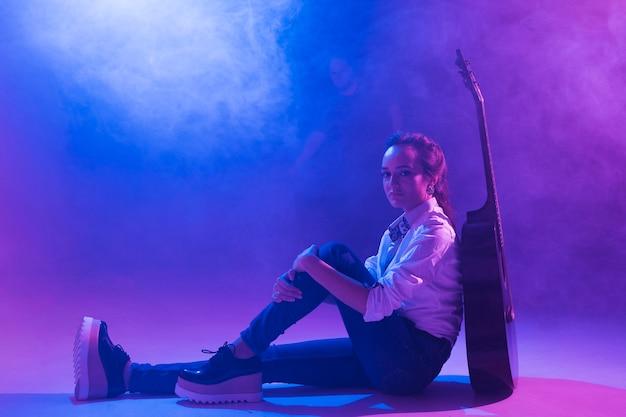 Artista no palco com violão Foto gratuita