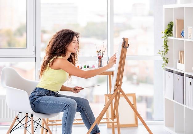 Artista sorridente pintura em cavalete Foto Premium