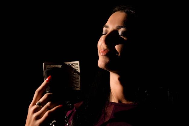 Artista vocal fêmea que canta em um estúdio de gravação. Foto Premium