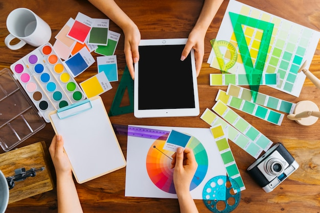 Artistas com tablet e clipboard na mesa Foto gratuita