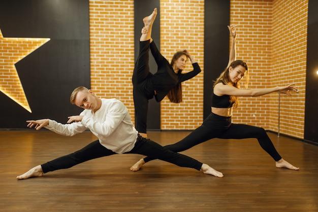 Artistas de dança contemporânea posam em estúdio. dançarinos femininos e masculinos treinando na aula, dança moderna, exercícios de alongamento Foto Premium