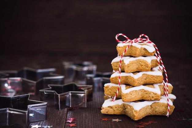 Árvore de biscoito de natal feita com pastrty de ano novo de gengibre de cortador de biscoito de estrela Foto gratuita