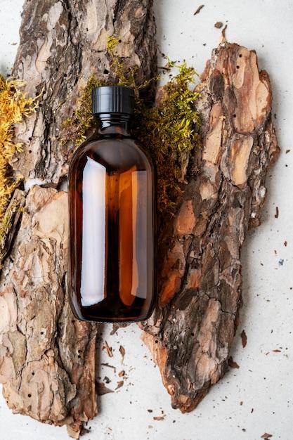 Árvore de casca natural da beleza, musgos minúsculos e grama de produtos cosméticos orgânicos na garrafa marrom de vidro. lay flat, Foto Premium