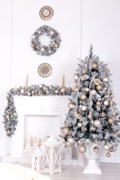 Árvore de natal com bolas de natal perto de lareira decorada Foto Premium