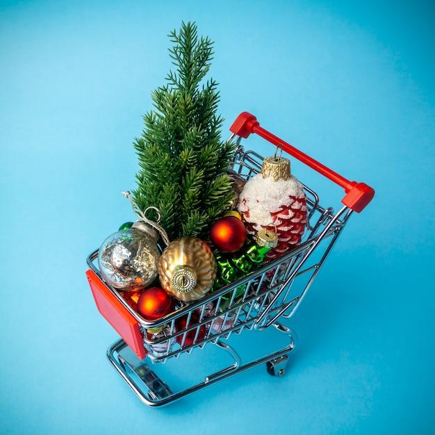 Árvore de natal com enfeites em um carrinho de supermercado. conceito de compras e venda de natal Foto Premium