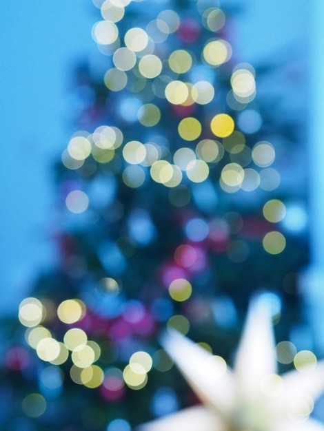 Árvore de natal com luzes desfocadas e estrela Foto Premium