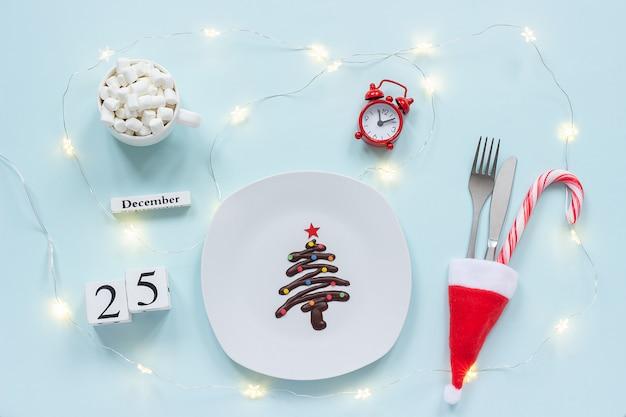 Árvore de natal de chocolate doce no prato, talheres no chapéu de papai noel, xícara de cacau, despertador e data Foto Premium