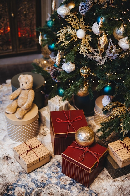 Árvore de natal decorada com bolas e muitos presentes sob a árvore do abeto Foto Premium