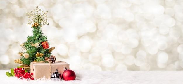 Árvore de natal e caixa de presente na luz de borrão bokeh Foto Premium