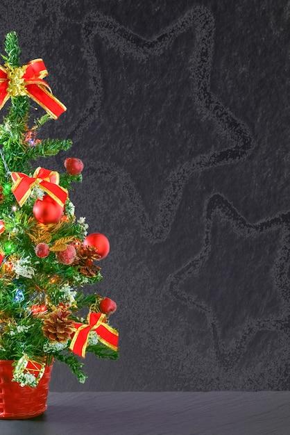 Árvore de natal pequena mesa decorada com enfeites vermelhos e laços em um fundo cinza Foto gratuita
