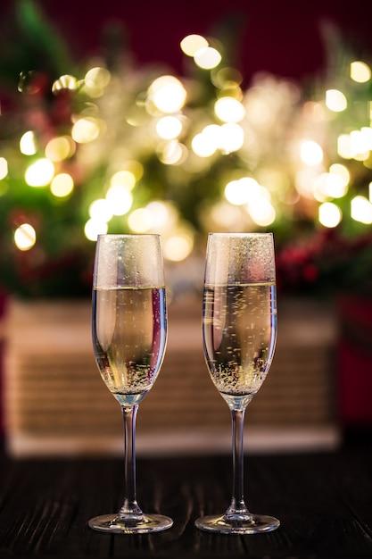Árvores de natal de composição de natal decoradas com luzes douradas, guirlandas, brinquedos e taças de champanhe vazias. Foto gratuita