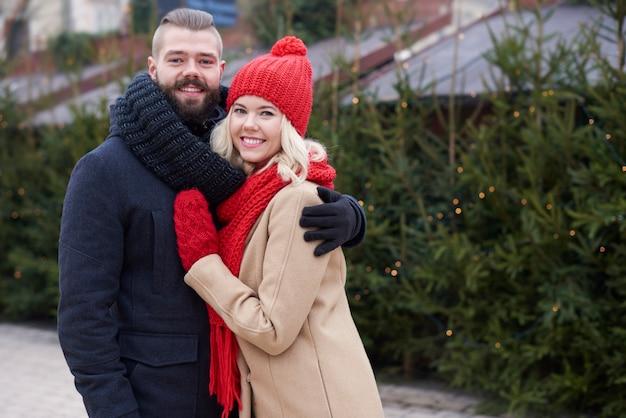 Árvores de natal frescas e jovem casal Foto gratuita