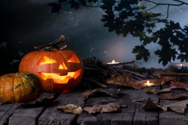 As abóboras de halloween dirigem a lanterna e as velas do jaque o na tabela de madeira em uma floresta místico na noite. projeto do dia das bruxas Foto Premium