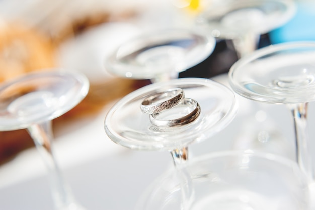 As alianças de casamento douradas com diamantes encontram-se acima em dos wineglasses eretos do lado para baixo. Foto Premium