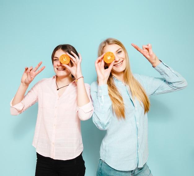 As amigas felizes riem e escondem seus olhos com fatias de mandarim sobre o fundo azul Foto Premium