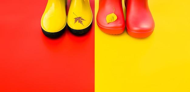 As botas de chuva das mulheres brilhantes em fundos coloridos com voado saem nas pontas. Foto Premium