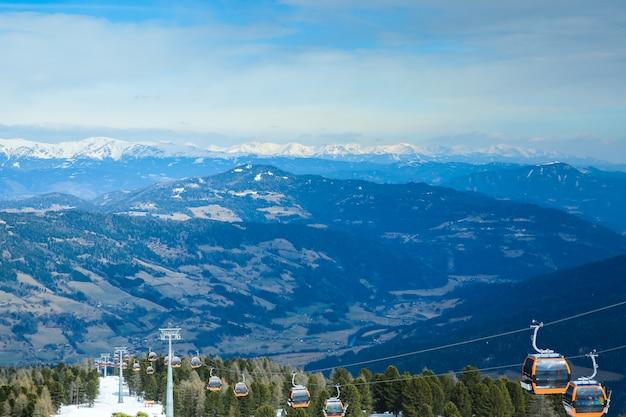 As cabines de gôndola laranja do teleférico levantam nas montanhas nevadas do inverno fundo belas paisagens Foto Premium