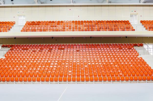 As cadeiras alaranjadas estão em uma fileira em um estádio coberto. tribuna para fãs Foto Premium