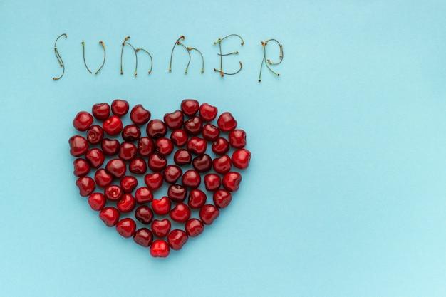 As cerejas vermelhas da baga dão forma ao coração e ao texto verão no fundo azul copie o espaço Foto Premium