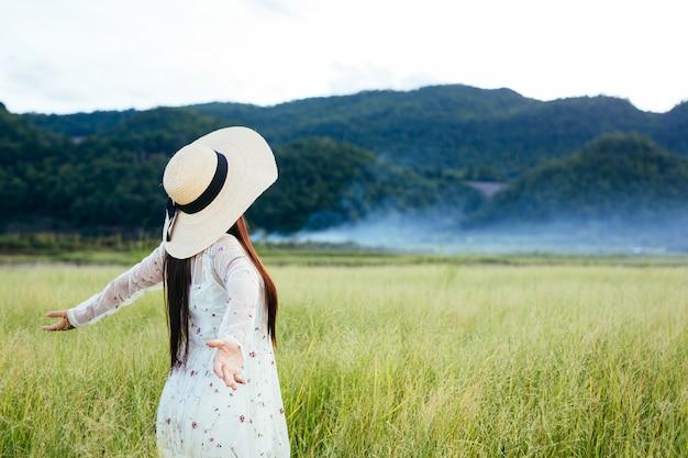 As costas de uma mulher bonita que está feliz no prado com uma grande montanha como um. Foto gratuita